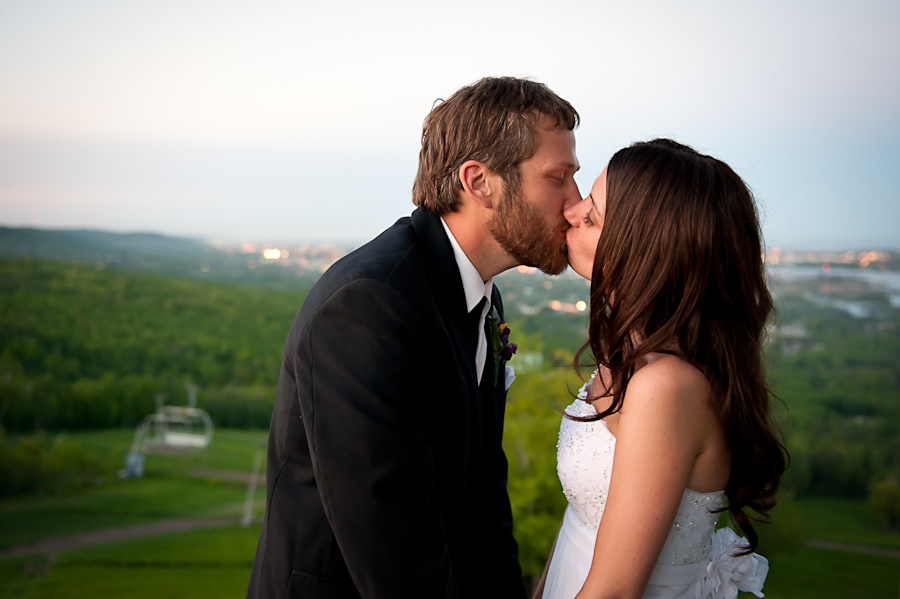 Bride and groom share a kiss at sunset during their Spirit Mountain wedding