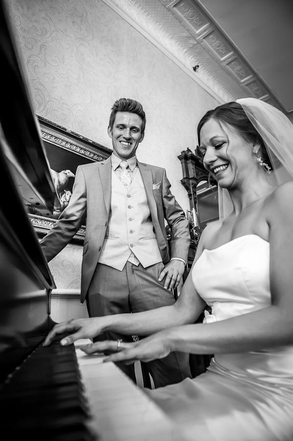 bride plays the piano while the groom smiles in the lobby of the St. James Hotel on their wedding day