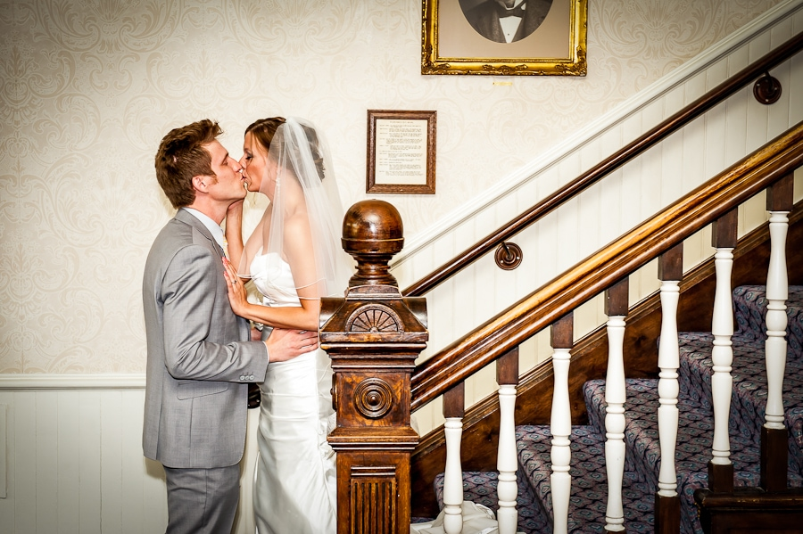 Couple kisses at the bottom of the Grand Staircase at the St. James Hotel shortly after their first look and moments before heading to their wedding ceremony