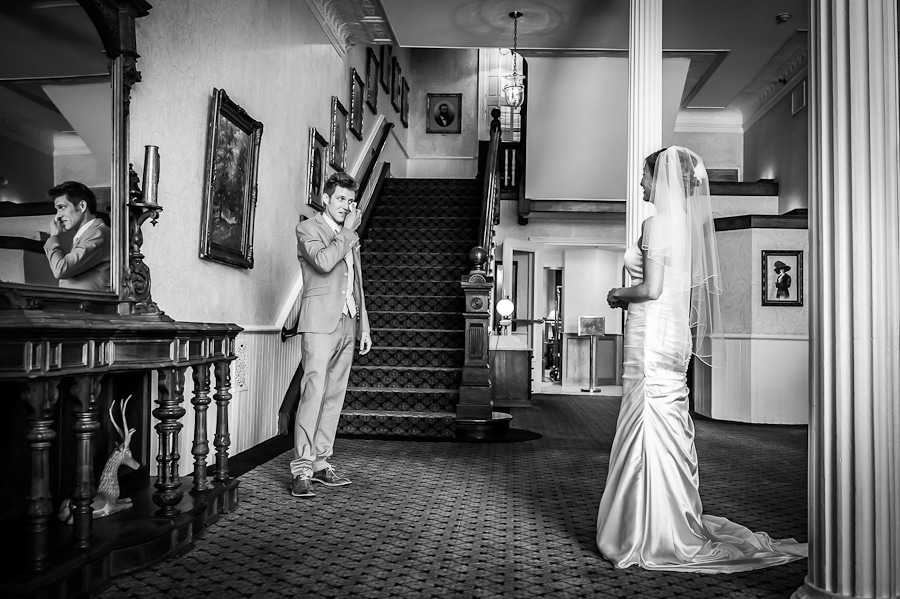 bride and groom share their first look at the bottom of the Grand Staircase in the lobby of the St. James Hotel on their wedding day