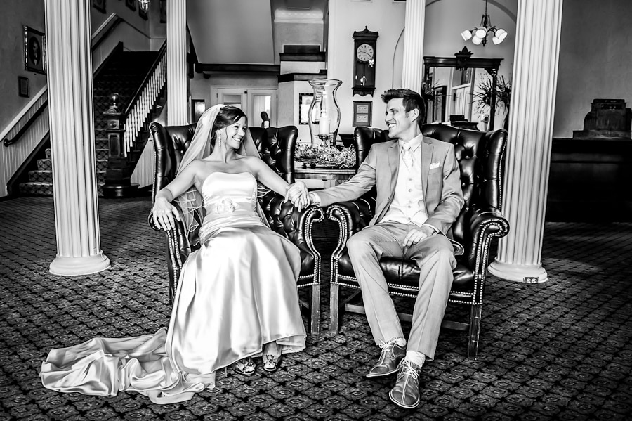 Couple sitting in the fancy historic chairs of the St. James Hotel lobby on their wedding day and smile at each other