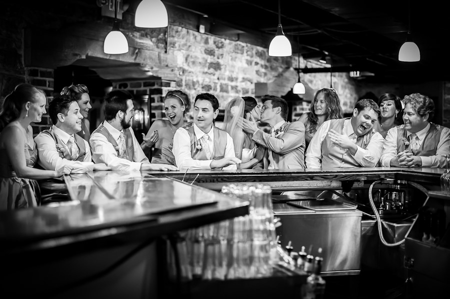 Large edding party group laughs and talks together at the historic bar inside of the St. James Hotel during a Red Wing, MN wedding
