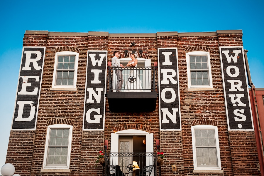 Bride and groom share sweet private moment on the balcony of the St. James Hotel on their wedding day with a view from street level shooting up at the couple in the historic brick building with the Red Wing Iron Works sign showing with a blue sky in the background