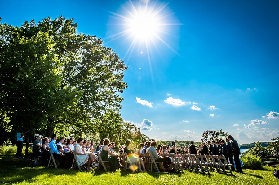 Wide angle view of the ceremony site overlooking the lake with the bright sun overheard