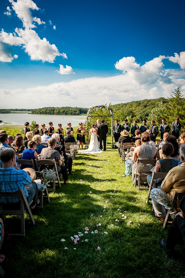 Bride and Groom stand at the alter to be married, with the lake and forest in the background, on a beautifully sunny day