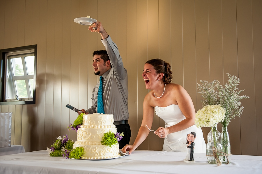 Bride & Groom cut their wedding cake and share a big laugh
