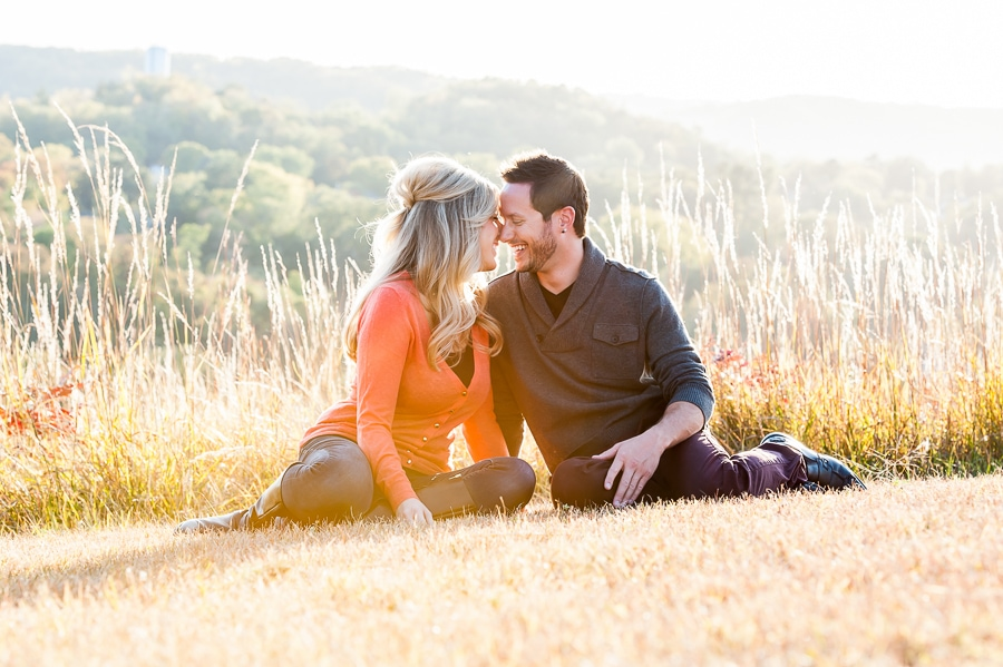 couple sitting forehead to forehead while smiling during their engagement session in Red Wing, MN at Memorial Park