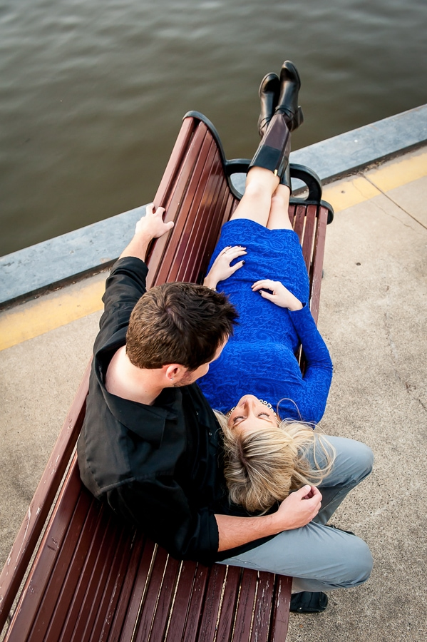 Overhead shot of a newly engaged couple as they lay on the bench at Levee Park in Red Wing, MN during their engagement photos