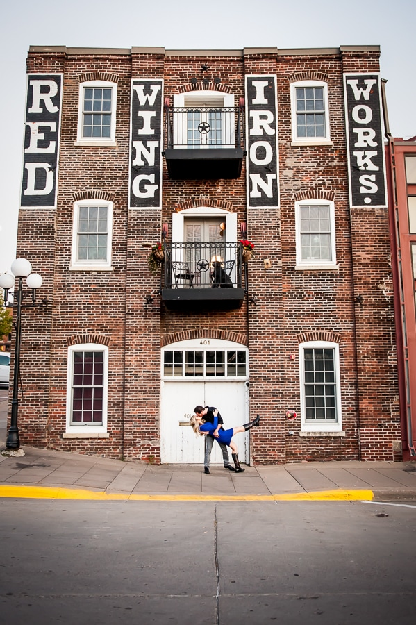 Engagement photo of a couple as the man dips his fiancé and kisses her behind the St. James Hotel in Red Wing, MN