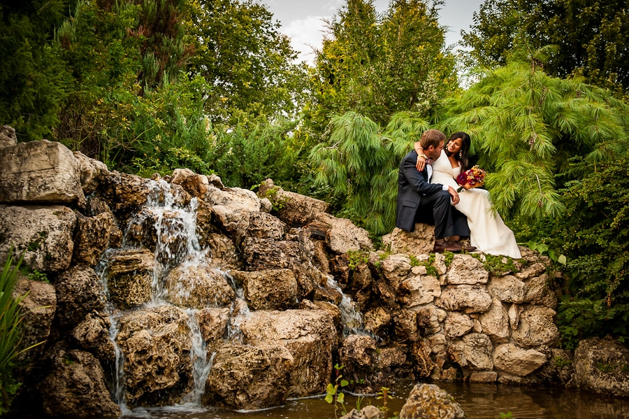 Newlyweds sit together closely on the rocks of the waterfall fountain at the Lyndale Park Peace Garden in Minneapolis right after their wedding ceremony