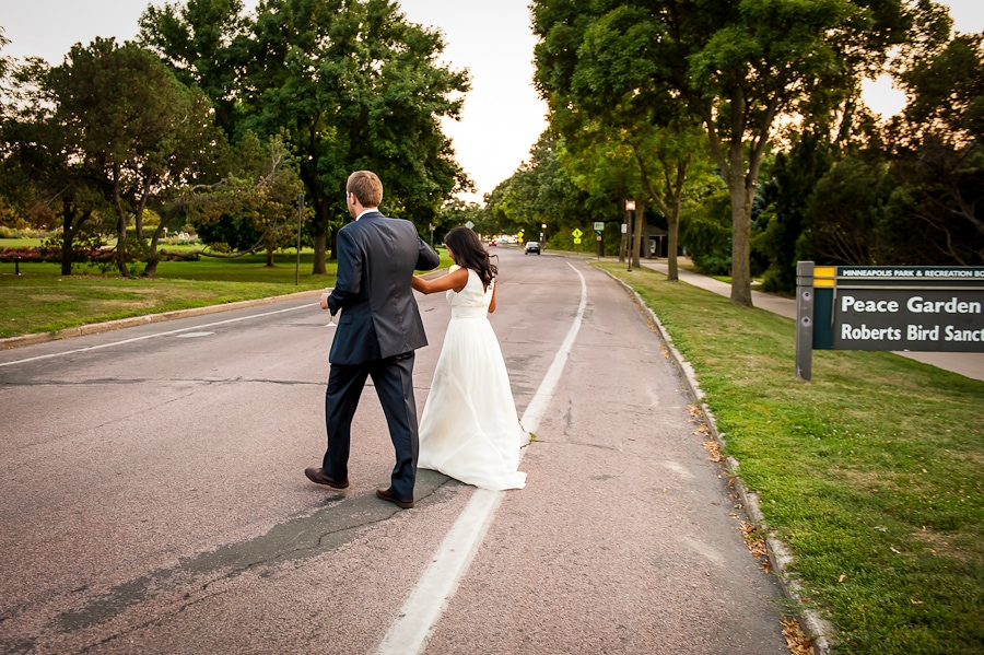 bride and groom cross the street on their way to the Rose Garden