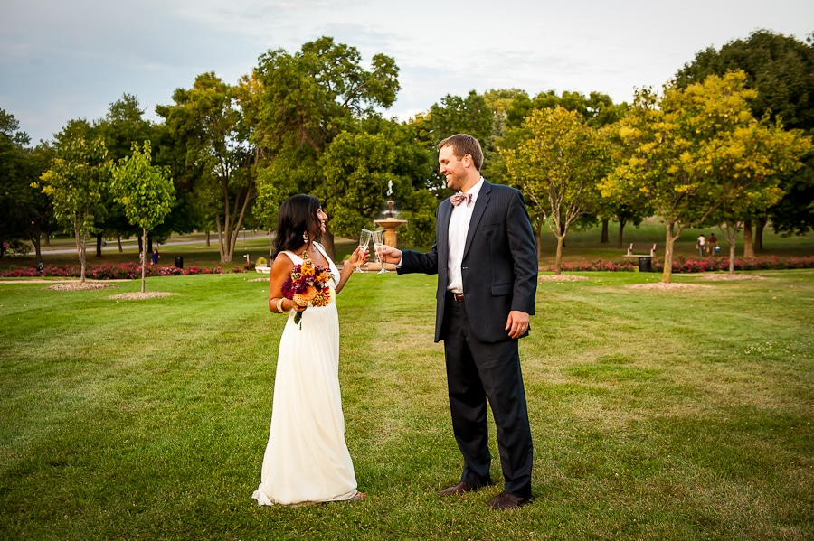 Couple cheers glasses at the Minneapolis Rose Garden post wedding ceremony