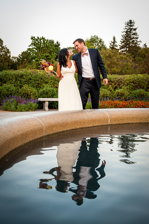 Couple smiling at teach other with their reflections shimmering across the Rose Garden fountain