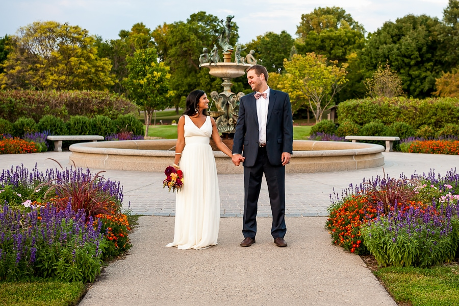 newlywed bride and groom hold hands and smile widely at each other in front of the cool water fountain at the Minneapolis Rose Garden in Lyndale Park