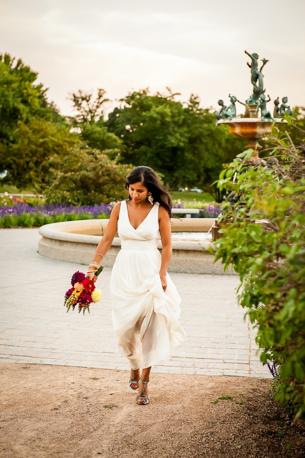 candid photo if bride walking near the fountain at the Lyndale Park Rose Garden