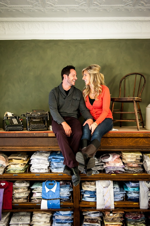 Couple sitting together and smiling hugely at each other on top of the large clothing racks inside Josephson's clothing store during their Red Wing engagement session