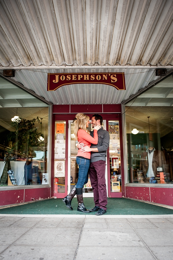 Newly engaged couple going in for the kiss in front of Josephson's clothing store in Red Wing, MN