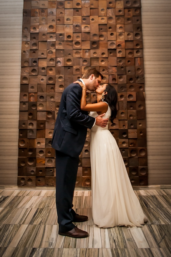 Couple kissed in front of cool wall art at the Graves hotel, their wedding reception location after their marriage at the Lyndale Park Peace Garden
