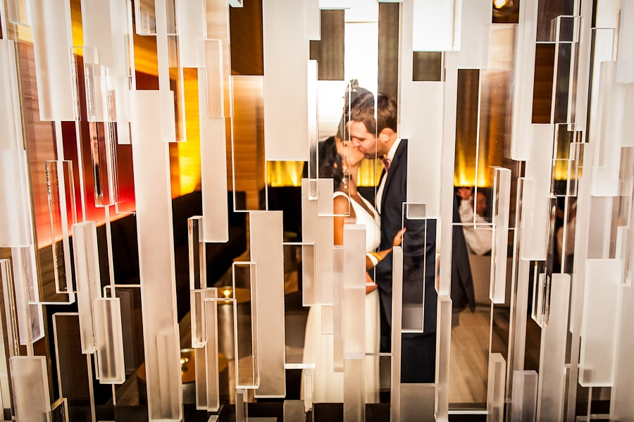 Creative image of a couple kissed thru the large glass art installation at the Graves Hotel post their wedding ceremony at the Minneapolis Peace Garden