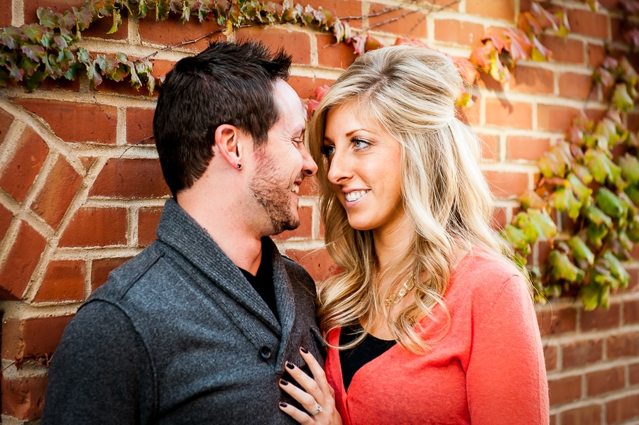 Couple gazes into each others eyes in a cool alley that features a brick wall that is covered in ivy