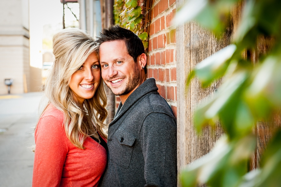 Couple smiling at the camera in a neat downtown Red Wing, MN alley that features a brick wall that is covered in ivy
