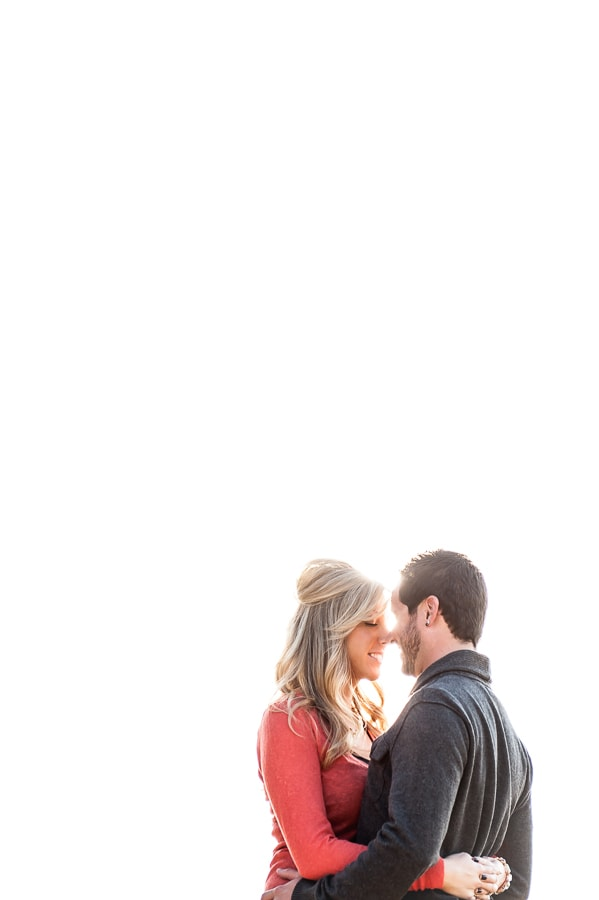 newly engagement couple holding each other close with a bright white sky behind them creating the illusion of empty space
