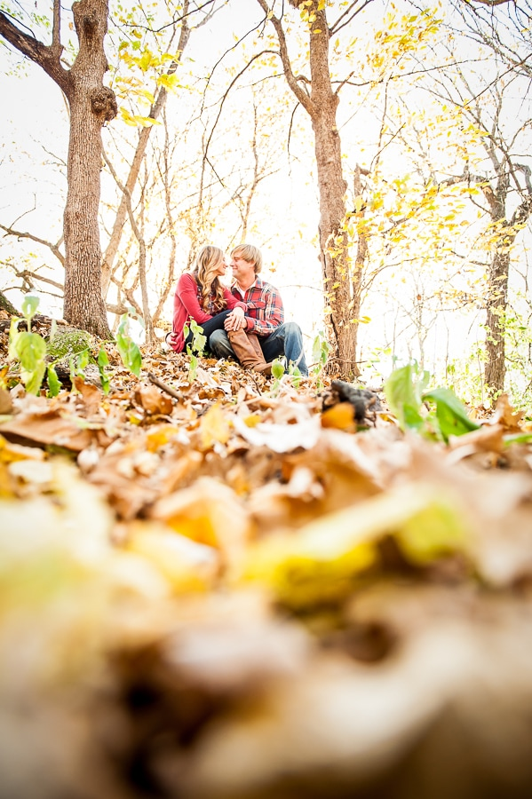 Newly engaged couple sitting on top of a frosted hill, amongst the leaves, during their engagement photos at Louisville Swamp