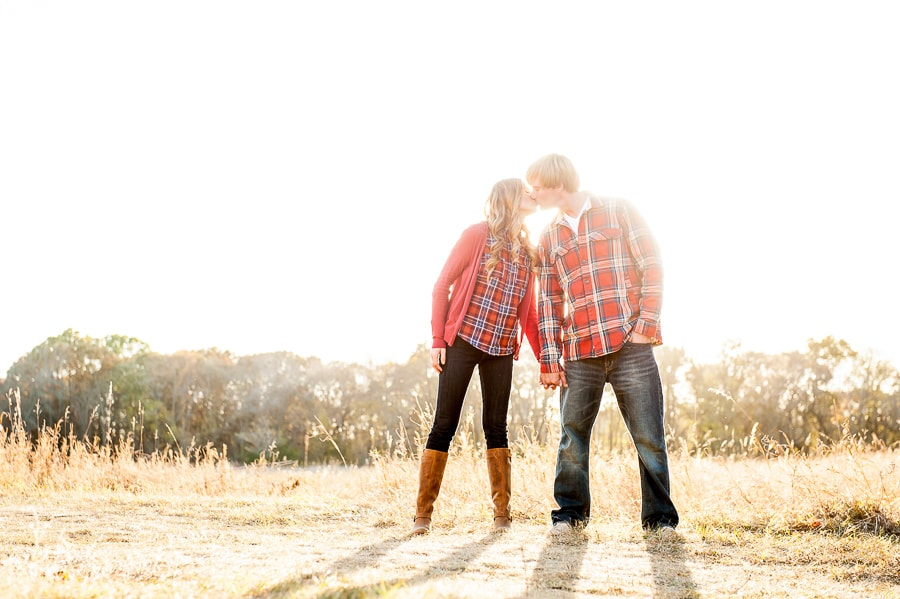 Couple kissing in their pink flannel shirts in an open prairie at Louisville Swamp in the Minnesota Wildlife Refuge Area during their engagement session