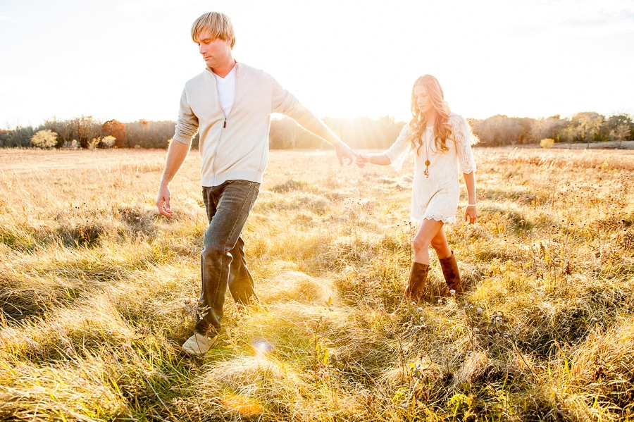 Couple holding hands as the walk across the prairie at Louisville Swamp at sunset during their engagement session