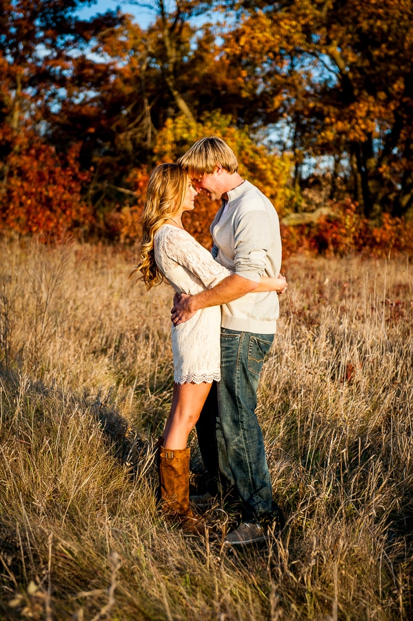Couple holding each other closely in the long prairie grasses of Louisville Swamp with the beautiful fall colors showing in the trees behind them