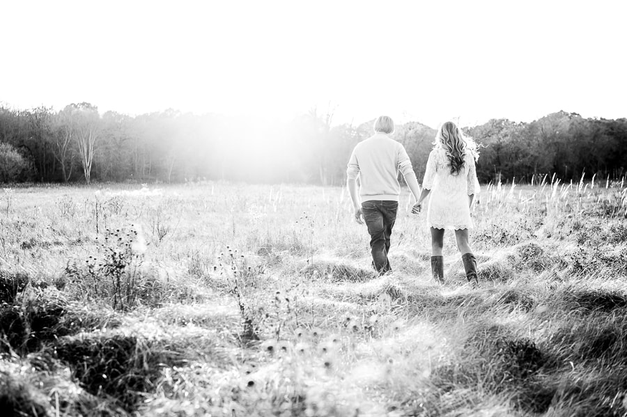 Balck & white photo of the couple walking away into a wide open prairie together as they head, hand-in-hand, toward their bright future together