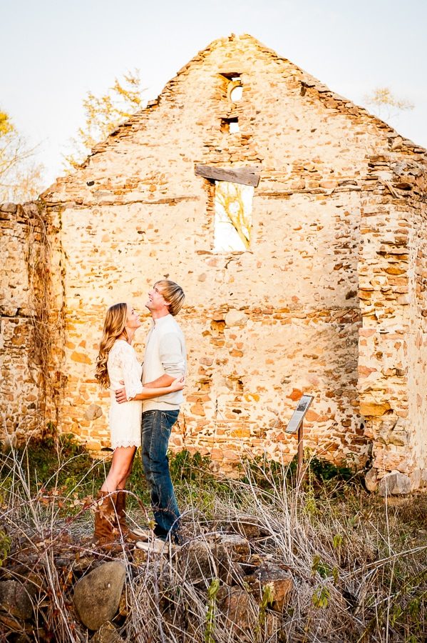 Couple shares a big laugh together with one of the coolest ruins at the Jabs Farm showing bending them in a large brick wall that still stands