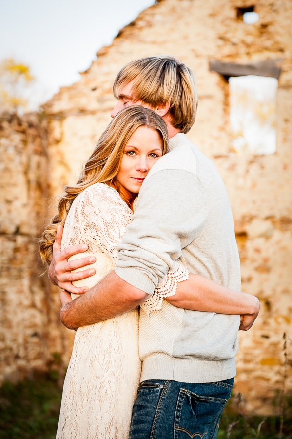Women gazing into the camera while her man holds her tight in his arms during their engagement session at Louisville Swamp with the gorgeous old brick wall ruins of Jabs Farm sits behind them