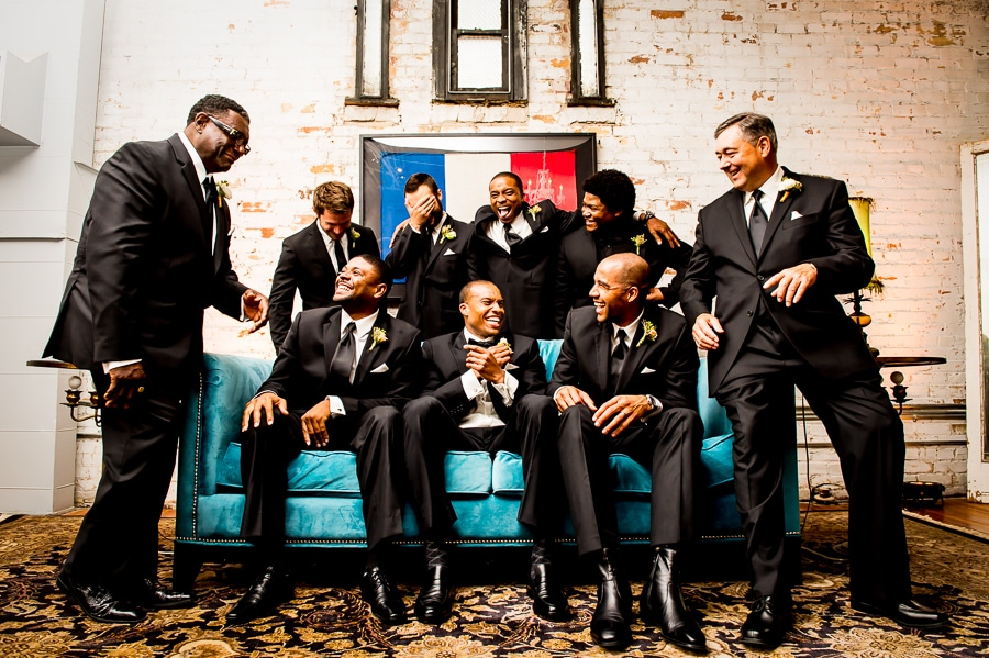 Groomsmen share a belly laugh in a colorful upstairs rooms at Aria in Minneapolis