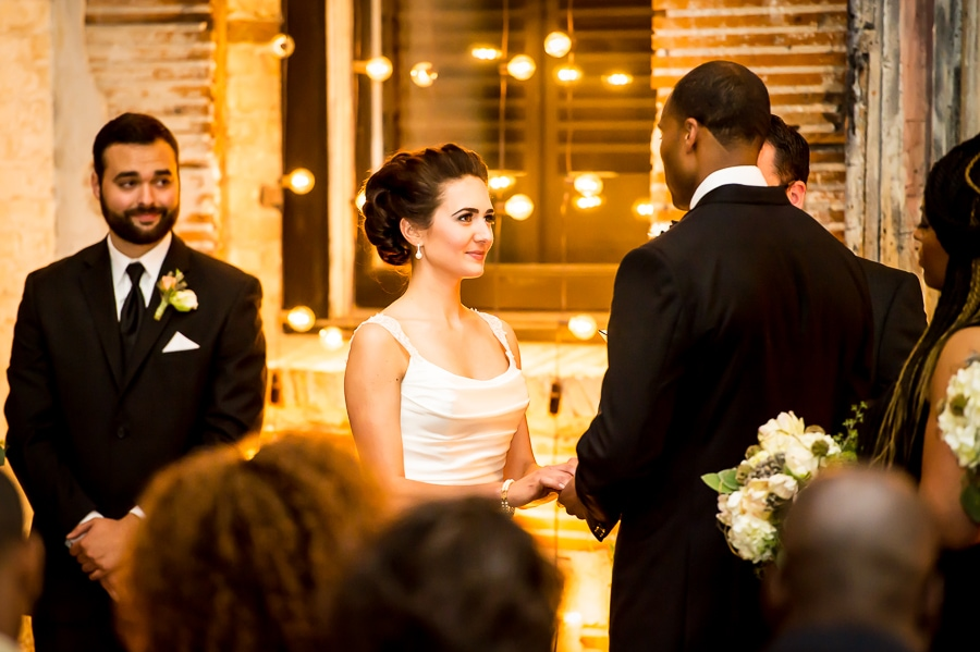 Close up of bride and groom during ceremony with string lights illuminating the background