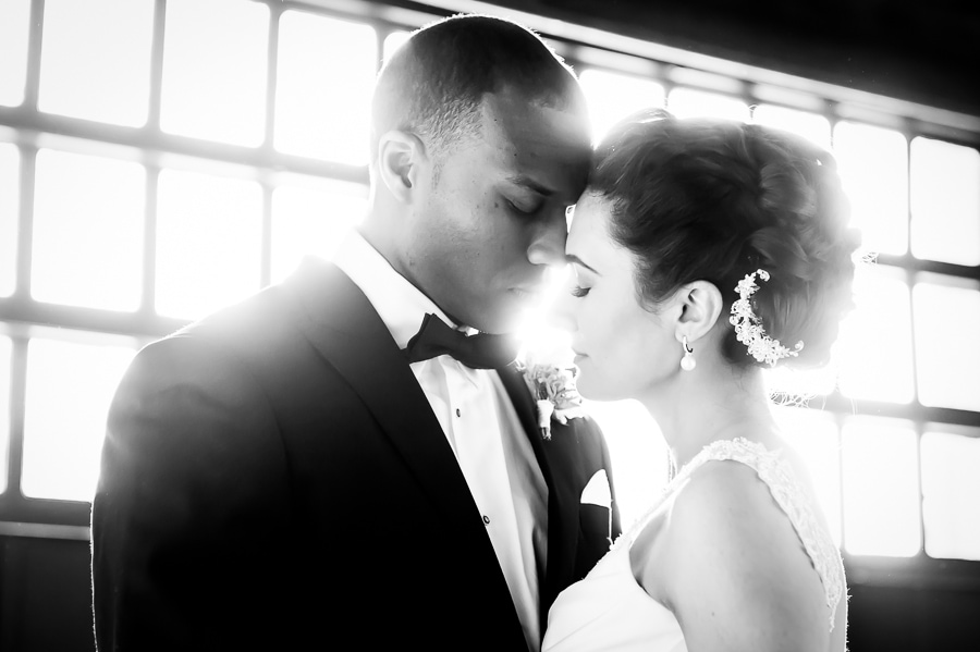 Brilliantly bright back lit window shot of bride and groom touching face to face