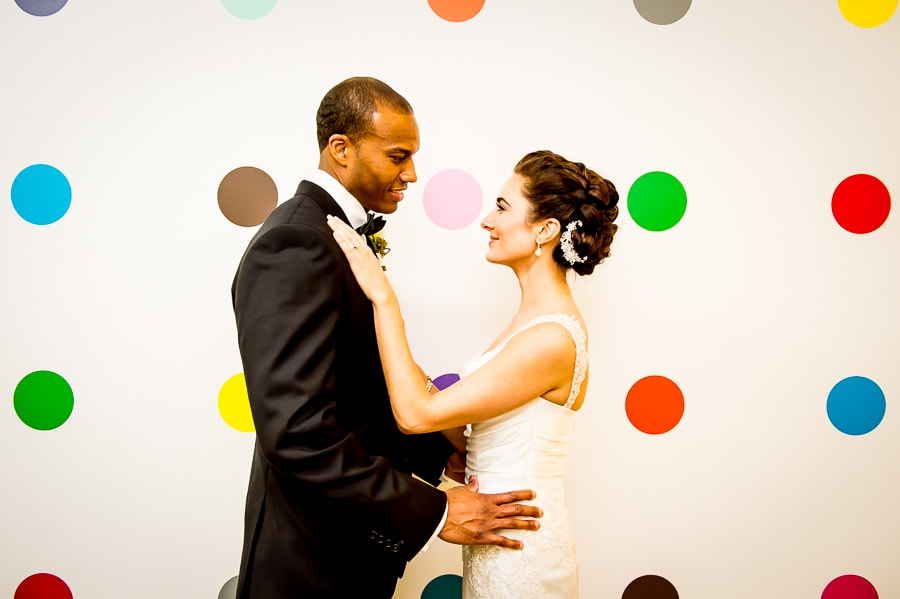 Couple hold each other in front of the polka dot wall at Aria