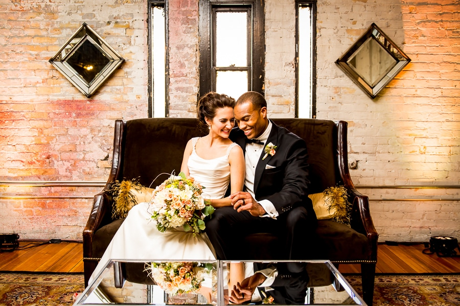 Newlyweds sit closely together on a cool couch in front of a mirrored table at one of the awesome rooms upstairs at Aria