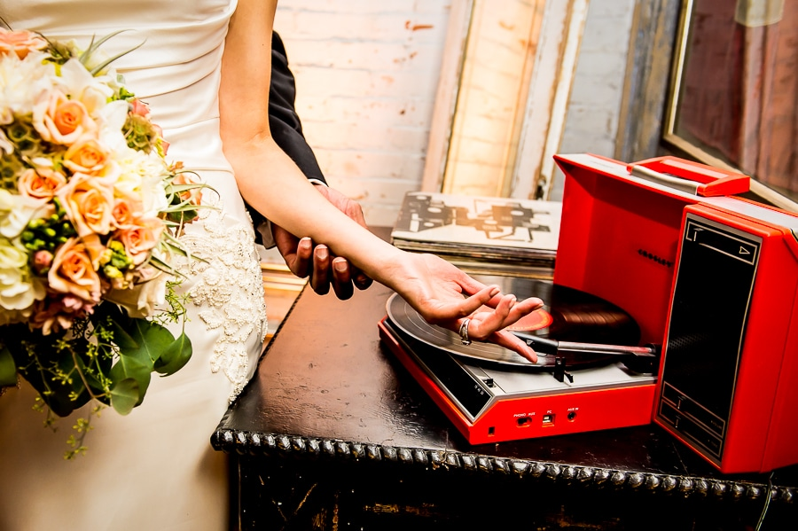 Groom gently caresses his brides arm as she positions the needle on an old colorful red record player at their music-themed Minneapolis Wedding at Aria