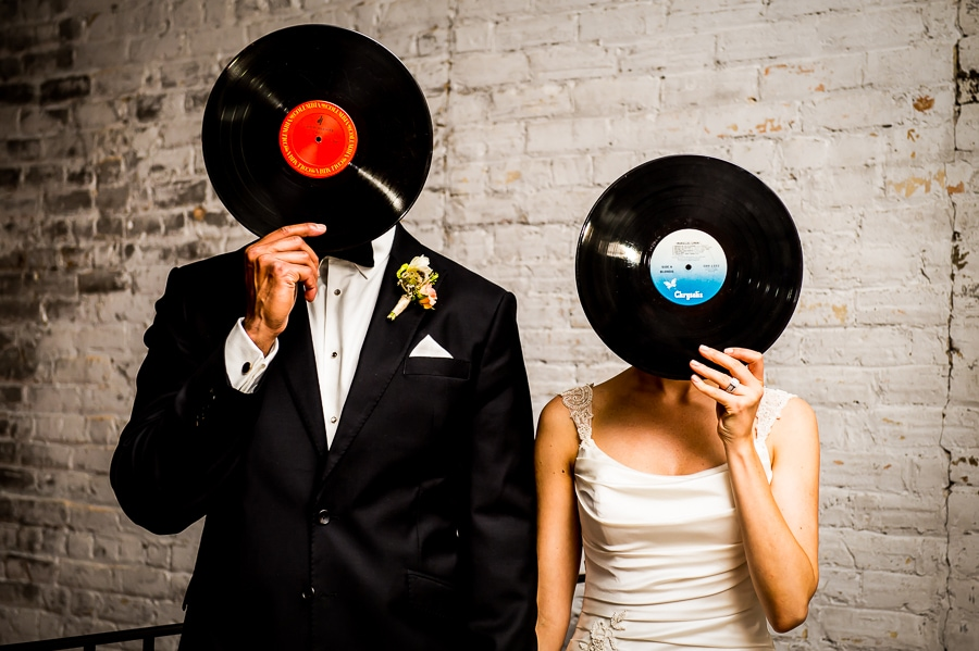 Bride and Groom hold up music record in front of their faces during their Minneapolis Wedding at Aria