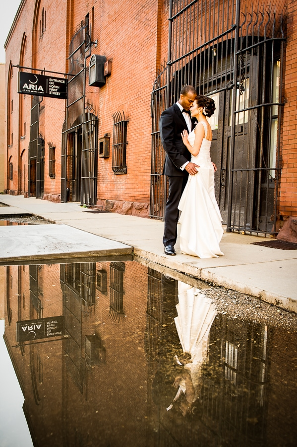 Couple holds each other close outside of Aria with their reflection in pool of water showing the cool red brick and Aria sign in the background