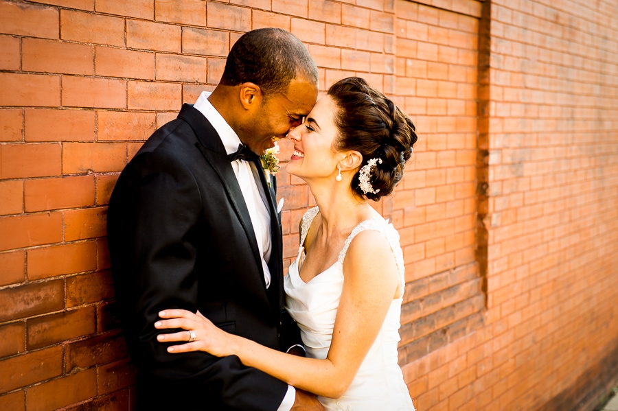 Bride and groom share a laugh along the red brick wall outside of Aria in Minneapolis