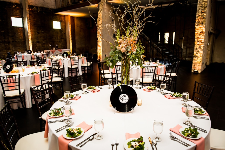Table setting for this music-themed Minneapolis wedding at Aria featuring records and flowers for centerpieces