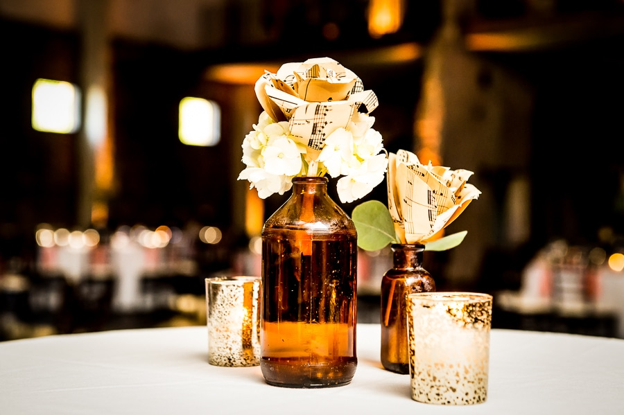 Sheet music turned into flowers used as centerpieces on the standing tables during the wedding reception at Aria