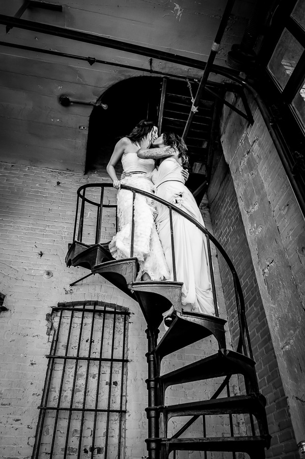 Two brides share a kiss on the spiral staircase at Aria during their same sex wedding in Minneapolis