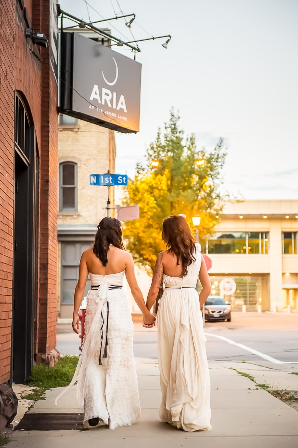 Brides walking underneath the Aria sign outside of the Minneapolis wedding venue