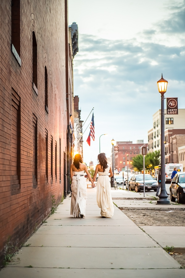Brides walking at dusk on their wedding day outside of Aria, along the side walk in the North Loop of Minneapolis