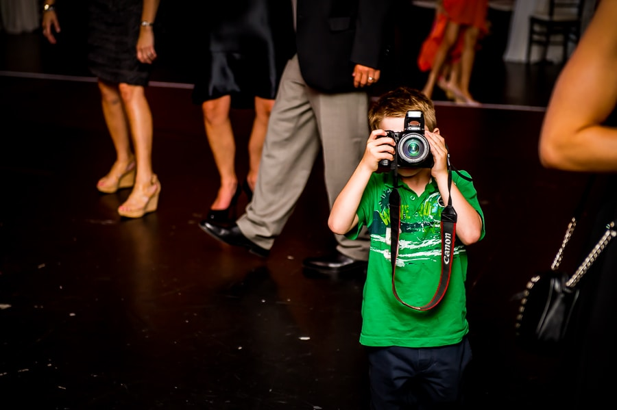 Young kid photographer in a bright green shirt takes a photo of me, the wedding photographer