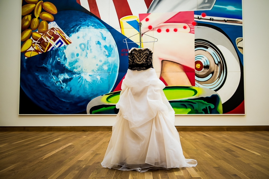 The bride's wedding dress hangs in front of large wall art installation at the Weisman Art Museum