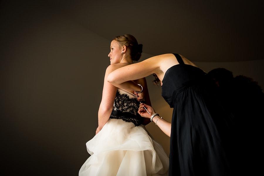 Bridesmaid helps the bride get into her wedding dress